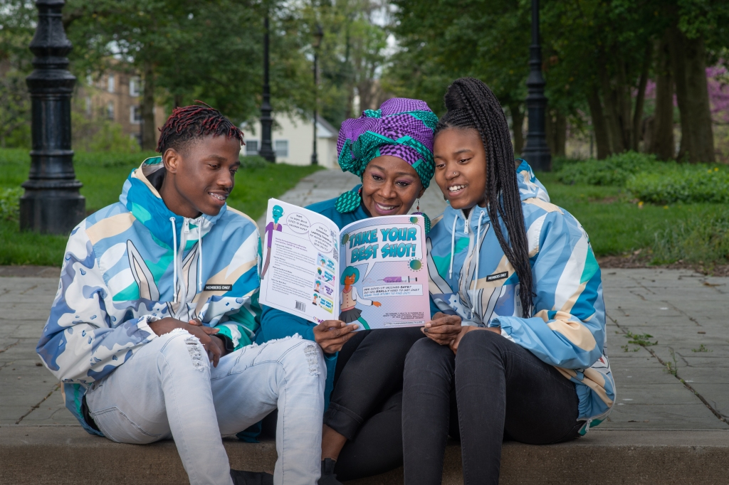 """Three teens read """"Take Your Best Shot,"""" one of the books distributed by the COVID Literacy Champions Program."""
